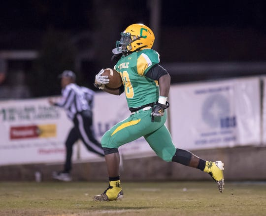 Waymond Jordan (28) carries the ball for a touchdown and a 14-0 Crusaders lead (after adding the extra point) during the Trinity vs Pensacola Catholic playoff football game at Pensacola Catholic High School in Pensacola on Friday, Nov. 15, 2019.