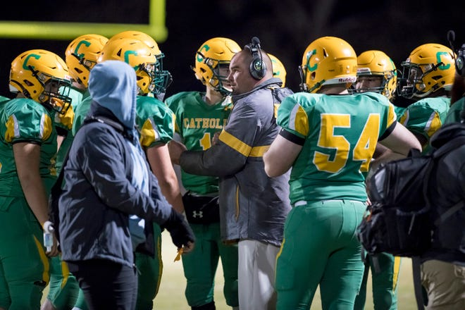 Head coach Matt Adams talks with his players in a timeout during the Trinity vs Pensacola Catholic playoff football game at Pensacola Catholic High School in Pensacola on Friday, Nov. 15, 2019.