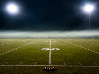 Smoke from smoke bombs settles over the field before a high school football game between Arizona Lutheran Academy and Phoenix Christian Preparatory School at Arizona Lutheran on Friday, Oct. 25, 2019.