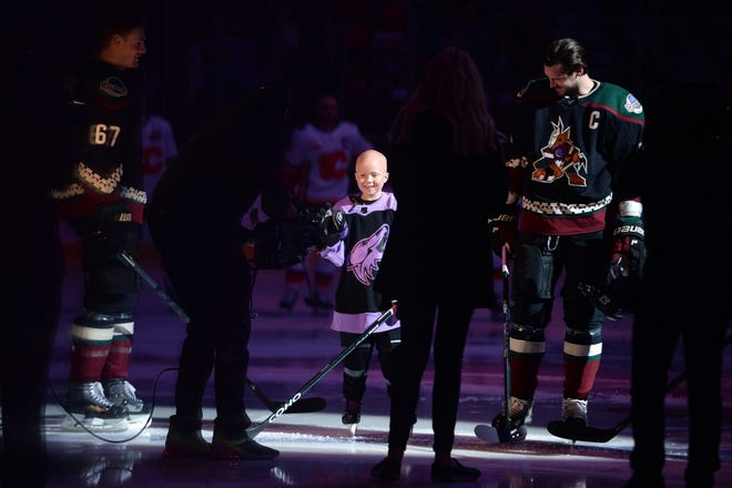Nov 16, 2019; Glendale, AZ, USA; Cancer patient Leighton Accardo joins the Arizona Coyotes during the national anthems prior the first period against the Calgary Flames at Gila River Arena.