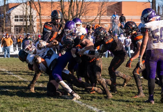 Saginaw Swan Valley quarterback Avery Goldensoph is tackled by players from Almont during the MHSAA Division 5 regional final Saturday, Nov. 16, 2019, at Almont High School.