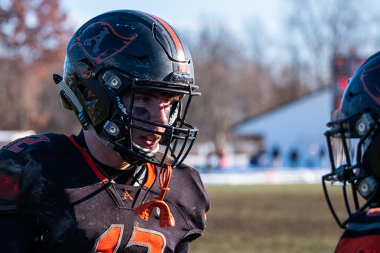 Almont quarterback Josh Hellebuyck talks with another player on the sideline of the MHSAA Division 5 regional final against Saginaw Swan Valley Saturday, Nov. 16, 2019, at Almont HIgh School.