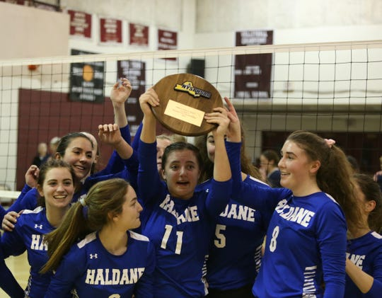The Haldane volleyball team hoists its plaque in celebration of winning the Class D regional semifinal on Nov. 15.