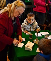 Volunteer Elizabeth Stein, left, of Jackson Township, stamps cards for visitor Nicoli Carbone, 5, during the York County History Center's Articles of Confederation Day at the Colonial Courthouse Complex in York City, Saturday, Nov. 16, 2019. Dawn J. Sagert photo