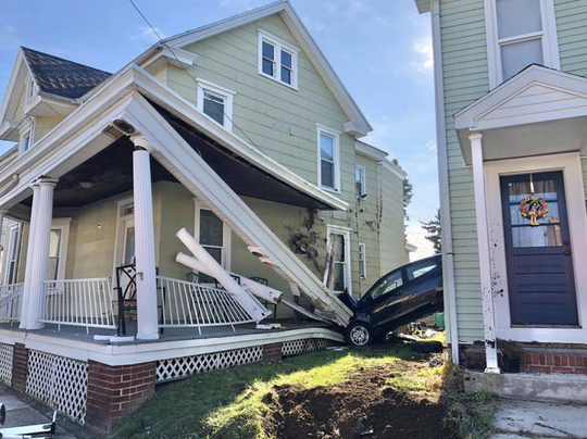 A passenger vehicle became lodged between two homes on Friday afternoon after striking a set of concrete steps.