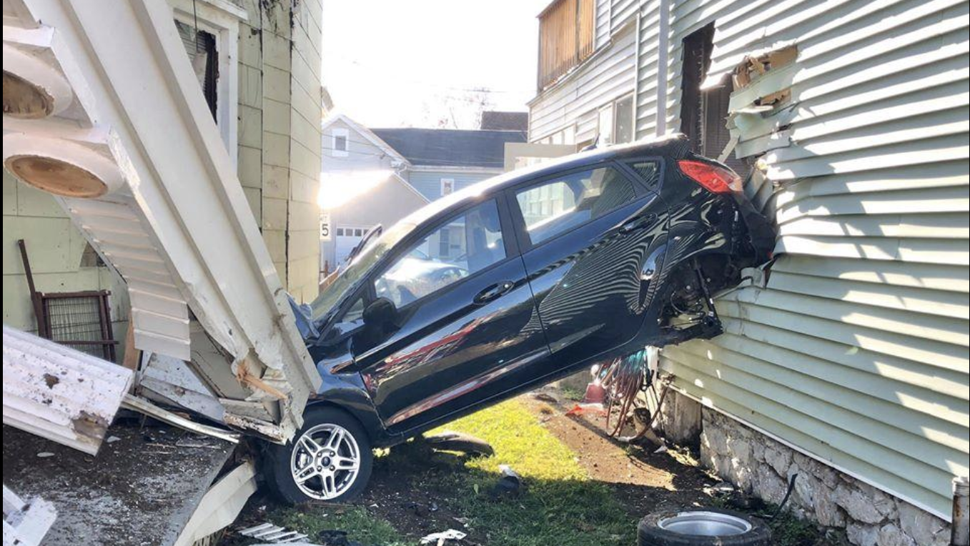 Car lodges between two houses, killing driver
