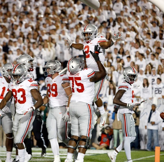 Ohio State's J.K. Dobbins (2) is lifted up by teammate Thayer Munford (75) after scoring against Penn State during the second half of an NCAA college football game in State College, Pa., Saturday, Sept. 29, 2018. Ohio State won 27-26. (AP Photo/Chris Knight)