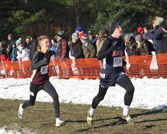 Pitssford Mendon's Colby Schenkel gets ready to pass Ton Cirrito to finish in 12th place at the Cross Country State Championships on Saturday.