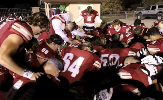 The West Valley football team says a prayer prior to its playoff game against Wheatland on Friday, Nov. 15, 2019, at a rock memorial that honors former Eagles players Jesse Brown and No. 8 Tyson Wacker.