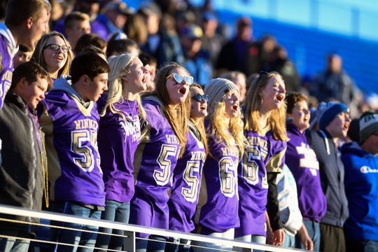 Winner fans, bathed in the light of sunset, cheer together during the Class 11B state football finals on Friday, Nov. 15, at the Dana J. Dykehouse Stadium in Brookings.