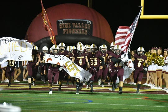 The Simi Valley High football team runs onto its home field before the start of its CIF-SS Division 10 semifinal game against Norte Vista on Friday night. The Pioneers won, 41-28, and will host Orange in a semifinal game next Friday.