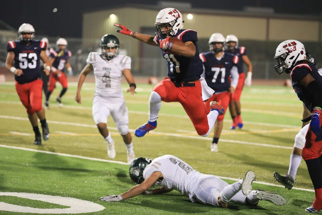 Tulare Western's Rolondo Holmes (11) hurdles over Dinuba's Brian Campbell during a Central Section Division II quarterfinal high school football game on Friday, November 15th, 2019.