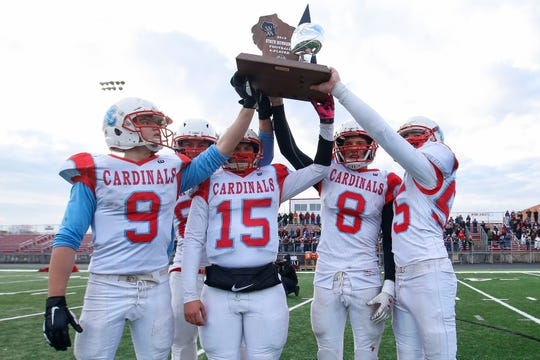 Newman Catholic captains Gavin Wulf (9), Joe Zeimetz (81), Ben Bates (15), Joe Stephan (8) and Matt Beck (55) hold up the runner-up trophy after the WIAA 8-player football championship game Saturday at Dorais Field in Chippewa Falls.