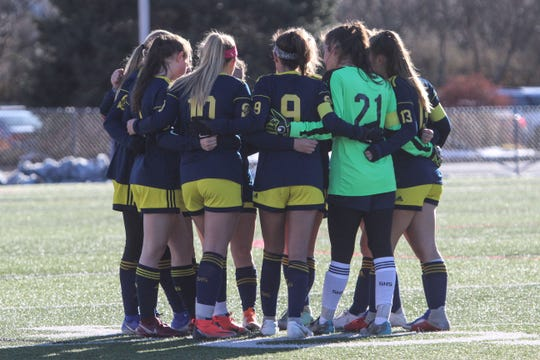 Spencerport huddles up before the final overtime period during the Class A state semifinals at SUNY Cortland on Saturday, Nov. 16, 2019.