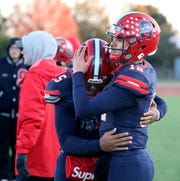 Archbishop Stepinac quarterback Joey Carino, right, is consoled by teammate Gary Wilkins during their loss to Cardinal Hayes in CHSFL AAA Championship game at Mitchel Field in Uniondale, New York, Nov. 16, 2019. Hayes beat Stepinac, 25-7.
