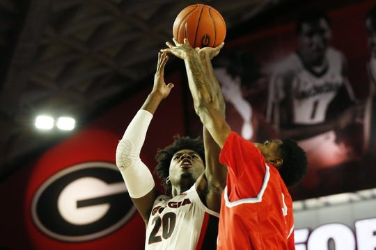 Georgia's Rayshaun Hammonds (20) takes a shot while being defended by Delaware State's Omari Peek-Green (2) during an NCAA college basketball game Friday, Nov. 15, 2019, in Athens, Ga.