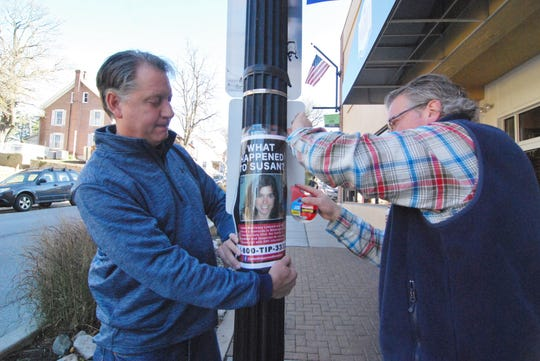 Susan's husband Ben Ledyard (left) helps hang a sign looking for information about his wife's killing.