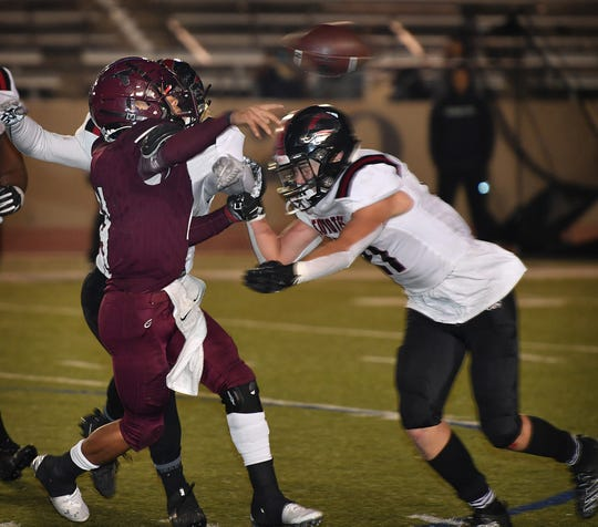 Wichita Falls High linebacker Ryan Murdock (21) and a teammate get to Fort Worth Northside quarterback Isaak Rosales (4) as he releases a pass during fourth quarter action Friday night. The Coyotes beat the Steers, 40-21, for the 5A Division 2 Bi-District Championship.