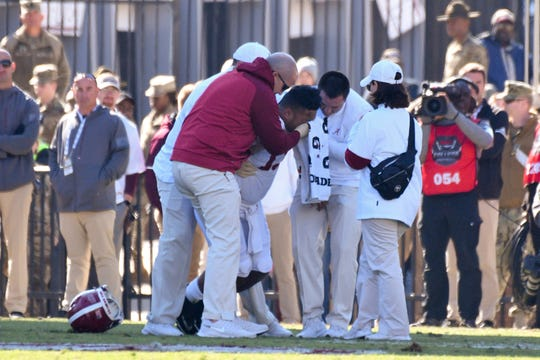 Alabama quarterback Tua Tagovailoa is assisted by team personnel after an injury during the second quarter against Mississippi State.