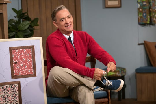 "Tom Hanks dons the red cardigan and comfy sneakers of the iconic Mister Rogers in ""A Beautiful Day in the Neighborhood."""