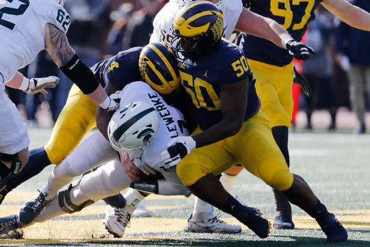 Michigan State quarterback Brian Lewerke is tackled by Michigan defensemen Michael Danna (4) and Michael Dwumfour in the first half at Michigan Stadium.