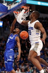 Seton Hall's Quincy McKnight (0) dunks as Saint Louis' Fred Thatch Jr. defends during the first half of an NCAA college basketball game Sunday, Nov. 17, 2019, in St. Louis. (AP Photo/Jeff Roberson)