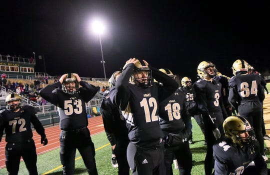 Corning's Jeff Yuelling (72), Danny Casper (53), Ben Wilcox (12) and teammates react with disbelief as Cicero-North Syracuse scores as time expired to win the Class AA regional football championship, with a final score of 24-22 on Saturday, November 16, 2019, at Vestal High School.