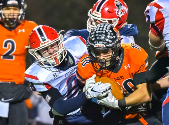 Lawrenceburg running back Adam Burd is tackled by Noah Mundy of Heritage Hills during a  IHSAA Playoff game at Lawrenceburg High School, Saturday, Nov. 16, 2019