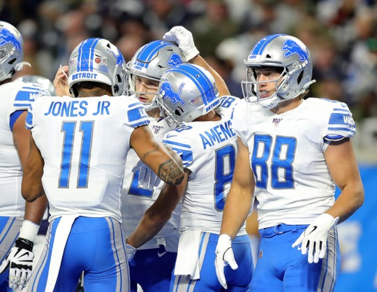 Lions quarterback Jeff Driskel, center, is congratulated by teammates after his touchdown against the Cowboys during the first half of the Lions' 35-27 loss on Sunday, Nov. 17, 2019, at Ford Field.