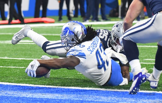 Lions running back Bo Scarbrough reaches over the goal line for a touchdown in the first quarter on Sunday.