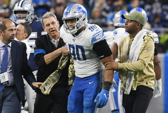 Lions' Trey Flowers is helped off the field after going down  in the fourth quarter.