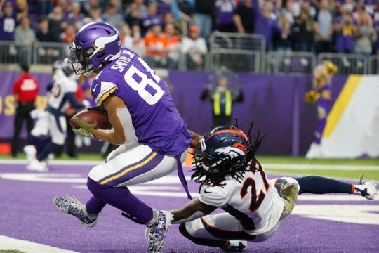 Vikings tight end Irv Smith (84) catches a 10-yard touchdown pass ahead of Broncos cornerback Davontae Harris, right, during the second half on Sunday.