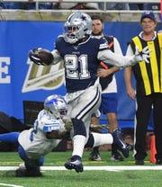 Cowboys' Ezekiel Elliott runs over Lions' Tavon Wilson on his way to a touchdown in the fourth quarter.