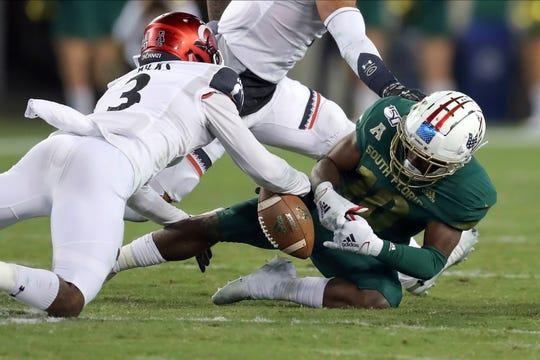 Cincinnati defender Ja'von Hicks strips the ball from South Florida's Kelley Joiner Jr. during the second half of an NCAA college football game, Saturday, Nov. 16, 2019, in Tampa, Fla. Cincinnati won 20-17.
