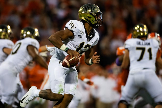 Wake Forest quarterback Jamie Newman (12) searches for an open teammate during their game against Clemson at Memorial Stadium Saturday, Nov. 16, 2019.
