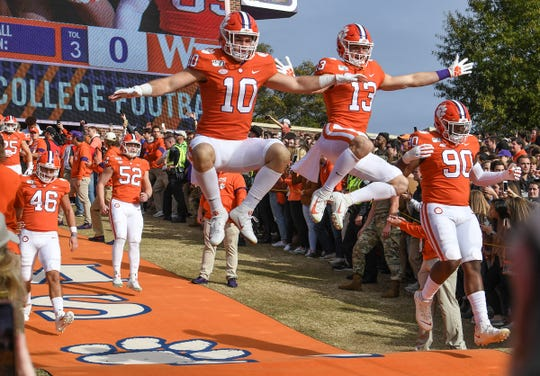 Clemson linebacker Baylon Spector (10) and wide receiver Brannon Spector(13) leap as players run down the hill before the game at Memorial Stadium in Clemson, South Carolina Saturday, November 16, 2019.