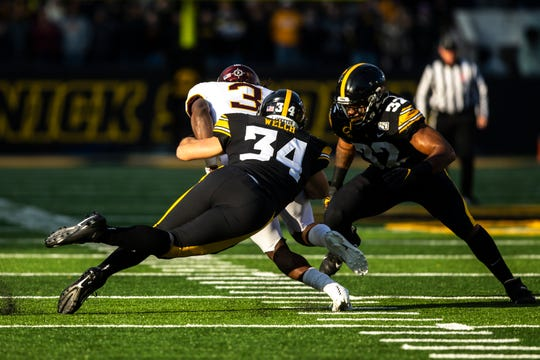 Iowa linebacker Kristian Welch (34) and Iowa linebacker Djimon Colbert (32) tackle Minnesota running back Cam Wiley (3) during a NCAA Big Ten Conference football game, Saturday, Nov., 16, 2019, at Kinnick Stadium in Iowa City, Iowa.