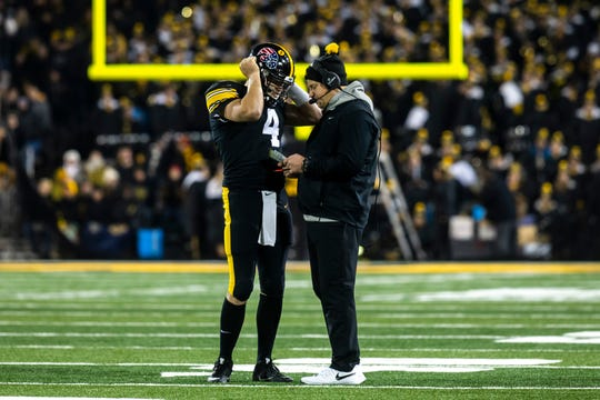Iowa quarterback Nate Stanley (4) talks with Iowa offensive coordinator Brian Ferentz during a NCAA Big Ten Conference football game, Saturday, Nov., 16, 2019, at Kinnick Stadium in Iowa City, Iowa.