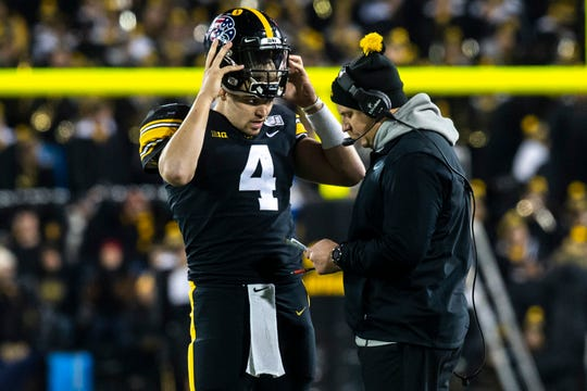 Iowa quarterback Nate Stanley removes his helmet to chat with offensive coordinator Brian Ferentz during a win over Minnesota. Next up for the senior is his final start at Kinnick Stadium, vs. Illinois on Saturday.