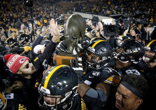 Tristan Wirfs hoists the Floyd of Rosedale Trophy over his right shoulder on his path to the happy Hawkeye locker room.