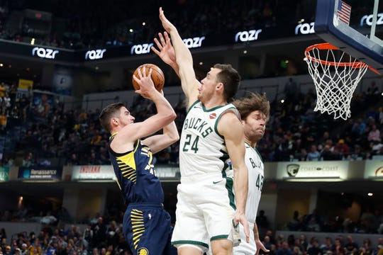 Nov 16, 2019; Indianapolis, IN, USA; Indiana Pacers forward TJ Leaf (22) takes a shot against Milwaukee Bucks guard Pat Connaughton (24) and center Robin Lopez (42) during the first quarter at Bankers Life Fieldhouse. Mandatory Credit: Brian Spurlock-USA TODAY Sports
