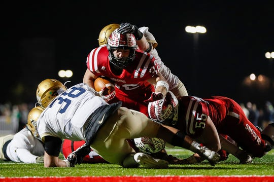 Jacob Brittsan (55) helped clear the way for Charlie Spegal (32) and the New Palestine offense in their regional win over Cathedral.