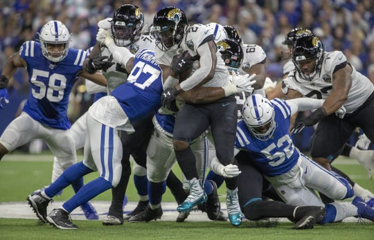 Leonard Fournette of the Jacksonville Jaguars is bottled up by Colts defenders, Jacksonville Jaguars at Indianapolis Colts, Lucas Oil Stadium, Indianapolis, Nov. 17, 2019.