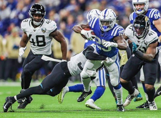 Indianapolis Colts running back Marlon Mack (25) fights for extra yards as he is tackled by Jacksonville Jaguars safety Jarrod Wilson (26) and linebacker Najee Goode (52) during the second quarter of the game against the Jacksonville Jaguars at Lucas Oil Stadium in Indianapolis, Sunday, Nov. 17, 2019.
