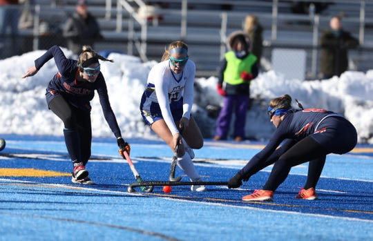 Horace Greeley's Kristen Graham and Lily Schoonmaker try and take the ball away from Maine-Endwell's Anna Castaldo during their state Class A field hockey championship game at Alden High School.  Maine-Endwell won, 2-1.