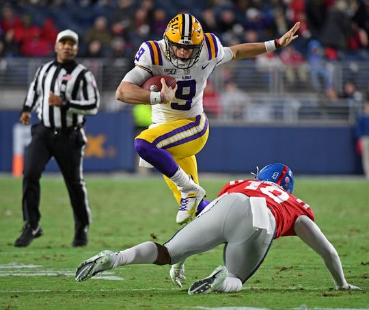 LSU quarterback Joe Burrow (9) strikes an inadvertent Heisman pose while avoiding Ole Miss linebacker Jacquez Jones (10) during the first half of a Southeastern Conference football game in Oxford, Miss., on Saturday night, Nov. 16, 2019. Burrow is a favorite to with the Heisman Trophy after this season. (AP Photo/Thomas Graning)