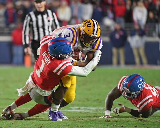 Mississippi linebacker Lakia Henry (1) tackles LSU running back Tyrion Davis-Price (3) during the first half of an NCAA college football game in Oxford, Miss., Saturday, Nov. 16, 2019. (AP Photo/Thomas Graning)