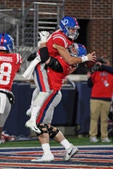 Mississippi quarterback John Rhys Plumlee (10) and offensive lineman Michael Howard (52) celebrate after a touchdown during the second half of the team's NCAA college football game against LSU in Oxford, Miss., Saturday, Nov. 16, 2019. LSU won 58-37. (AP Photo/Thomas Graning)