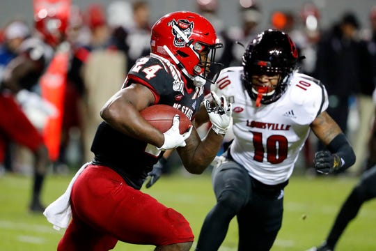 North Carolina State's Zonovan Knight (24) runs the ball away from Louisville's Rodjay Burns (10) during the first half of an NCAA college football game in Raleigh, N.C., Saturday, Nov. 16, 2019. (AP Photo/Karl B DeBlaker)