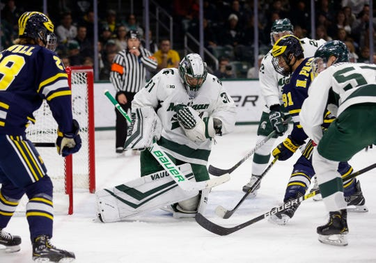 Michigan State goalkeeper John Lethemon, center, makes a stop and gloves the puck against Michigan's Emil Ohrwall, left, and Nick Pastujov (91), Saturday, Nov. 16, 2019, in East Lansing, Mich.